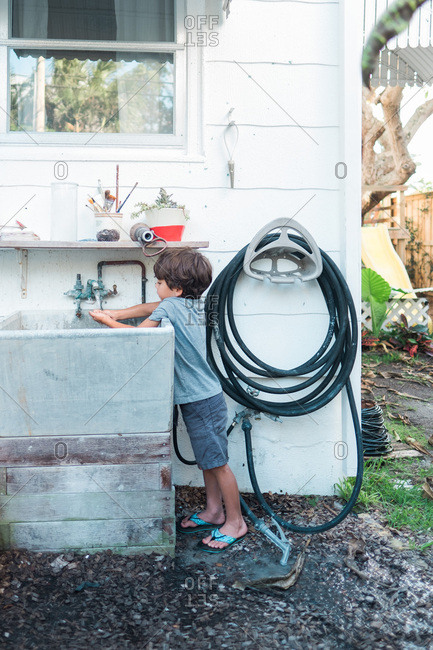 Young boy washing hands in outdoor sink before going inside for supper