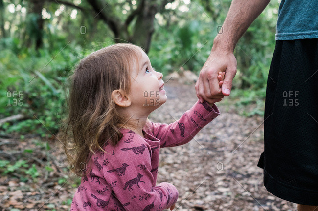 Little girl looking up lovingly at dad while holding hands in forest