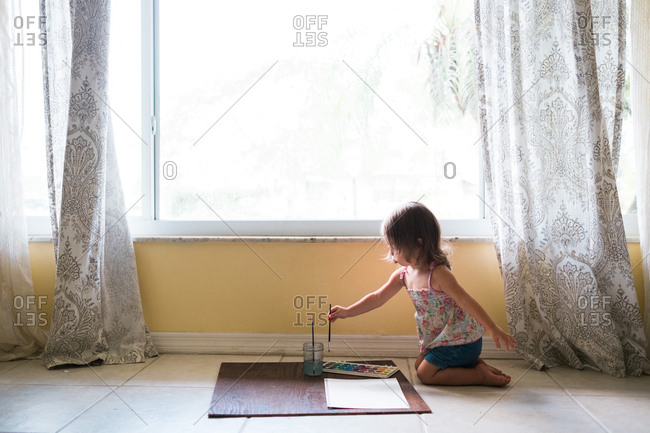 Wide shot of little girl kneeling on floor painting next to window