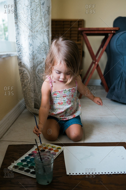 Little girl kneeling by window choosing color to use on painting