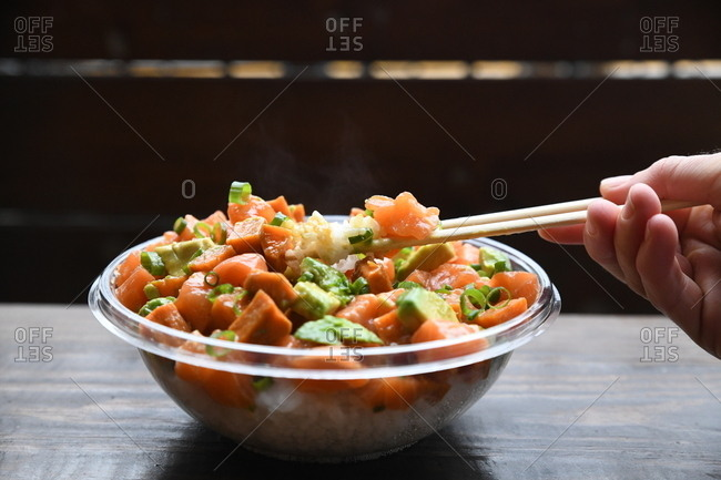 Person using chopsticks to eat salmon and avocado poke bowl