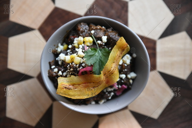 Poke bowl with black beans and corn topped with a zucchini slice