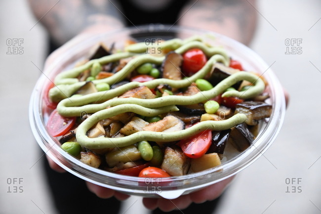 Person holding poke bowl with eggplant and topped with wasabi sauce