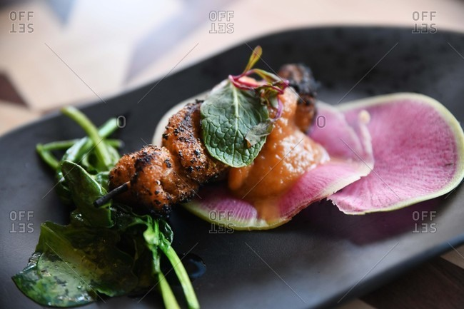 Meat on kebab topped with sauce and served with spinach and watermelon radish slices