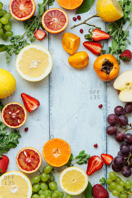 Overhead layout of colorful fruits on painted wood backdrop