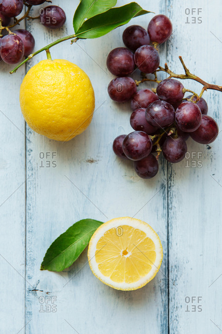 Whole and half lemon next to grapes on painted wood