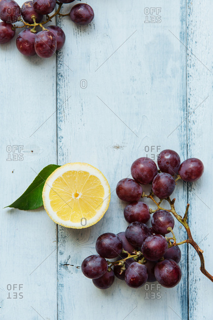 Halved lemon slice next to cluster of grapes