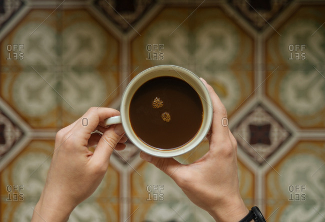 Top view of mug of coffee over patterned tile floor