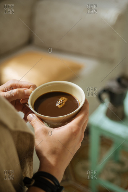 High angle view of hands holding fresh cup of coffee