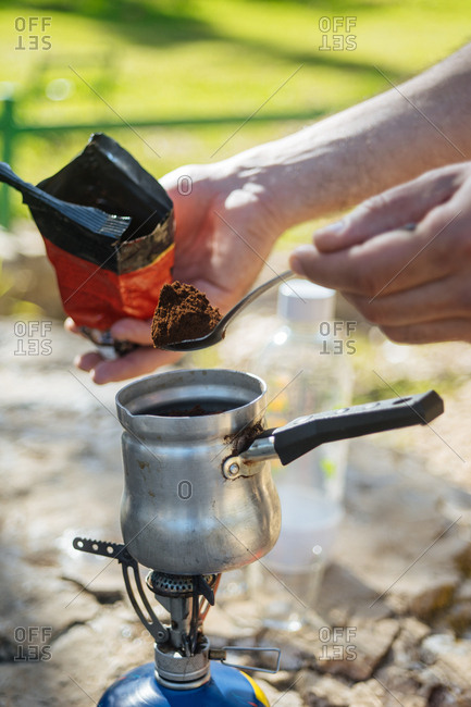 Man pouring coffee grounds into tin pot outside