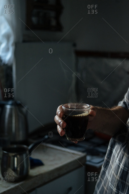 Man standing alone in dark kitchen with steaming glass of coffee