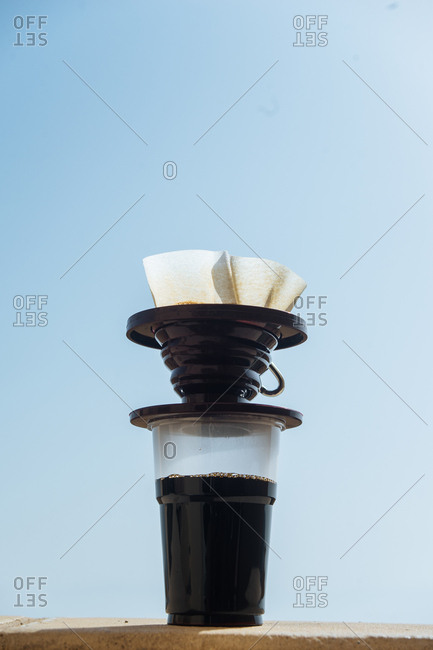 Coffee press on ledge in sunny day