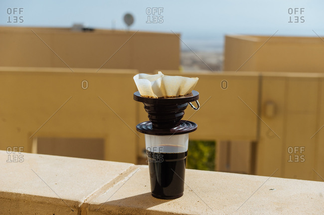 Single serve coffee brewing in sun on building ledge