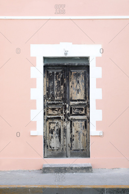 Weathered old door in freshly painted pink wall