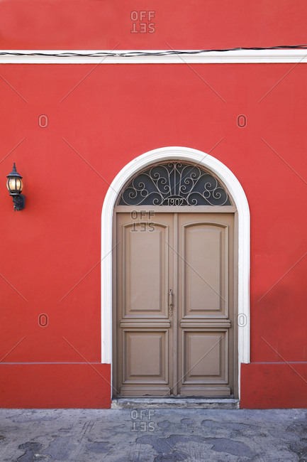 Ornate tracery in semi circular fanlight above double doors in red wall