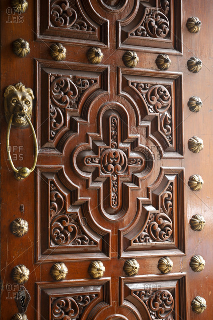 View of door with ornately carved panels and brass lions head door knocker