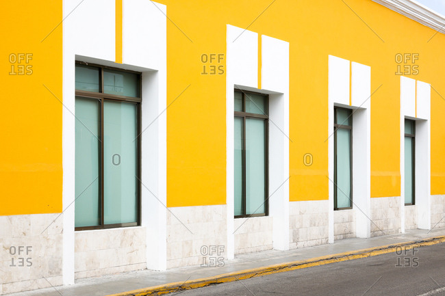 View of row of windows in bright yellow wall
