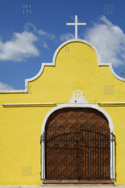 Detail of facade of small church painted yellow with white border