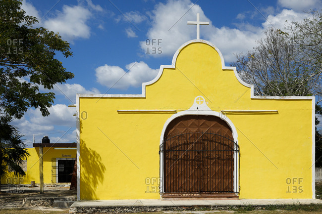 Exterior view of small church painted yellow with white border