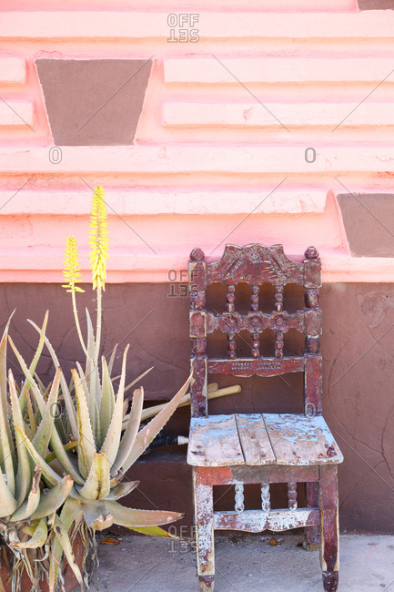Old weathered chair welcoming people to sit in the shade against pink wall
