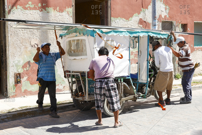 Celestun, Mexico - March 05, 2018: Workers tying down sheets of metal to top of auto rickshaw