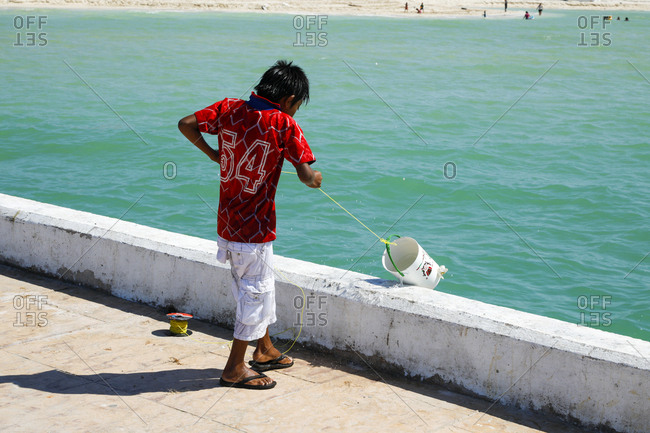 Young fisherman pulling bucket up from sea in Celestun, Mexico