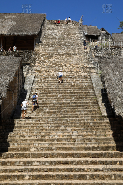Ek Balam, Mexico - March 07, 2018: Tourists climbing the stairs of the Acropolis
