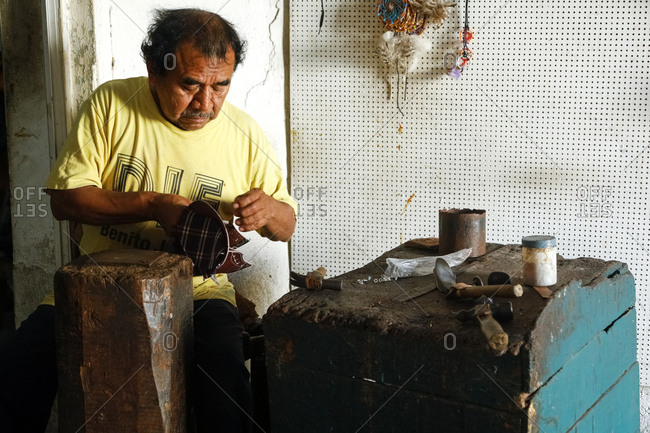 Valladolid, Mexico - March 07, 2018: Craftsman making leather sandals by hand in workshop