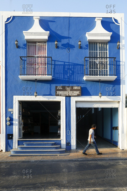 Valladolid, Mexico - March 07, 2018: Man walking by cheerful facade of funeral parlor