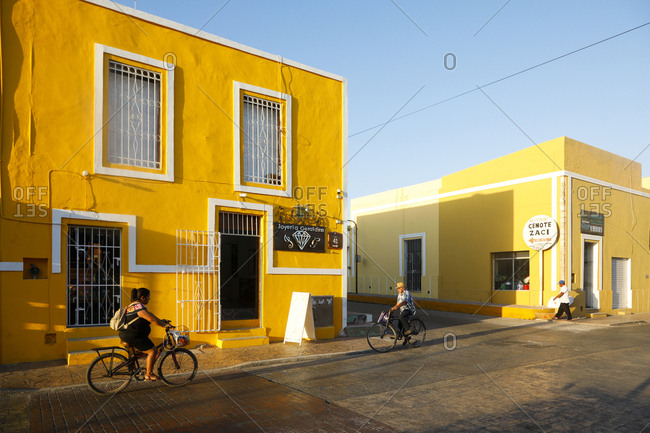Valladolid, Mexico - March 07, 2018: Local people cycling down quiet street past colorful buildings