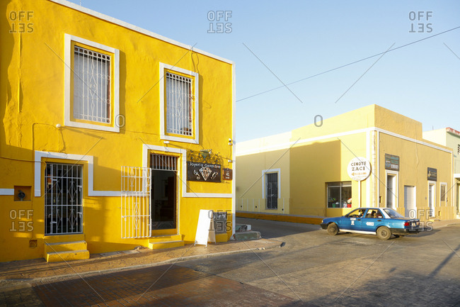 Valladolid, Mexico - March 07, 2018: Taxi driving down quiet street between colorful buildings