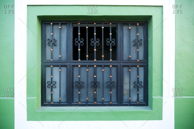 Ornate iron grill covering window in green wall in Valladolid, Mexico