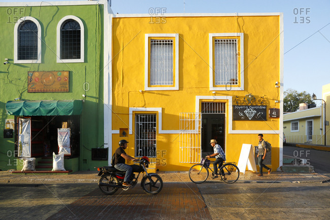 Valladolid, Mexico - March 07, 2018: People passing by colorful storefronts on quiet street
