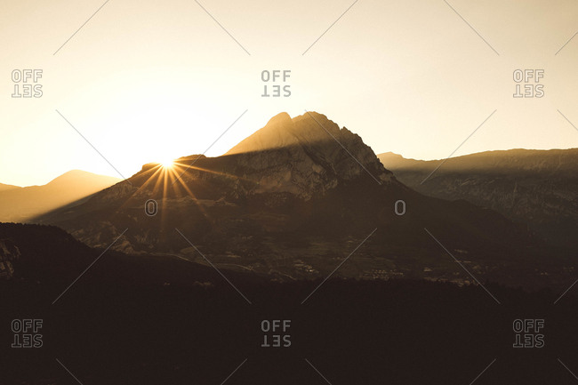 Beautiful view to high peaks in backlit and sunset in clear sky.