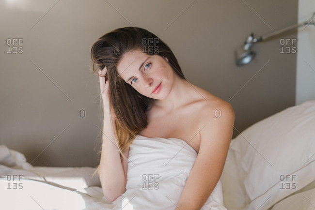 young naked woman wrapped in a sheet sit on bed