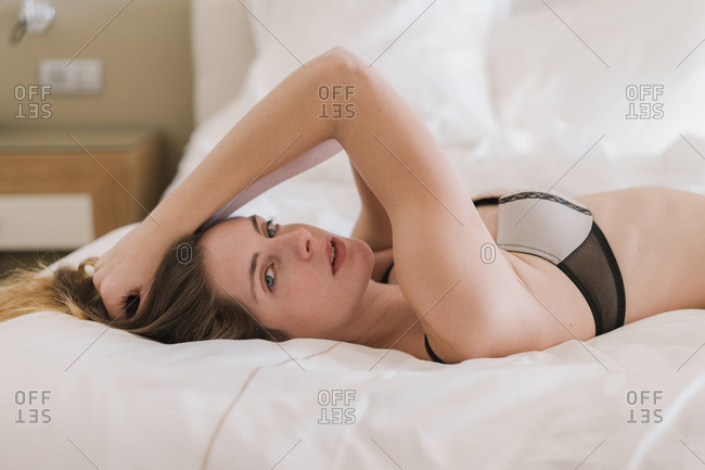 Attractive young woman in lingerie lying on bed and looking at camera.