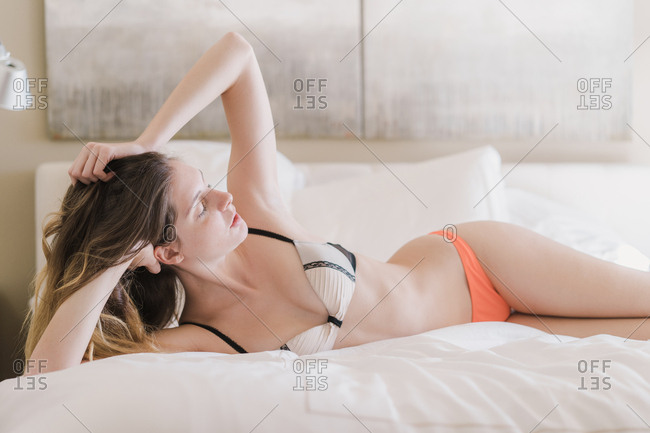 Attractive young woman in lingerie lying on bed
