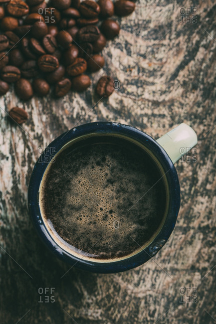 Coffee cup with coffee beans on dark background