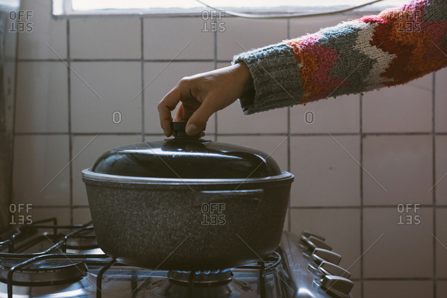 Pot on gas fire, woman cooking with her hand on the lid of the pot