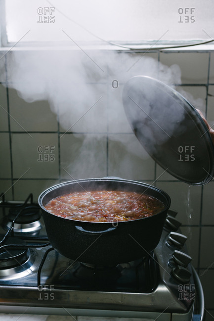 Steam stew, when lifting the lid, in the old kitchen