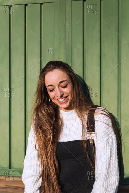 Cheerful pretty young woman looking at camera and adjusting hair at wooden wall.