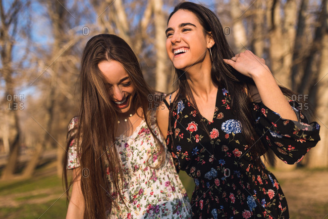 Two smiling young pretty women standing in sunny woods together.