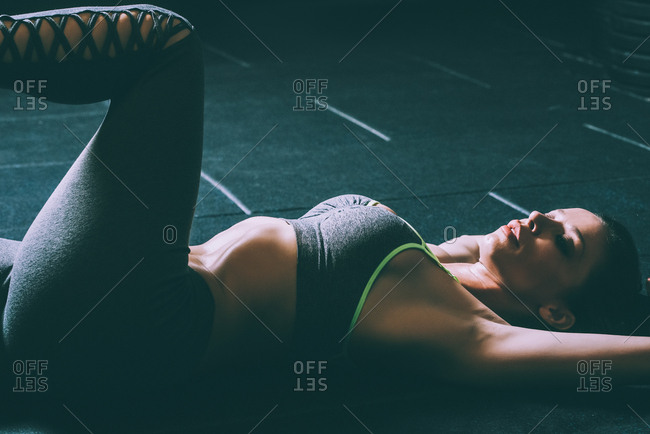 Fit blonde woman lying on the floor stretching and doing crunches in gym