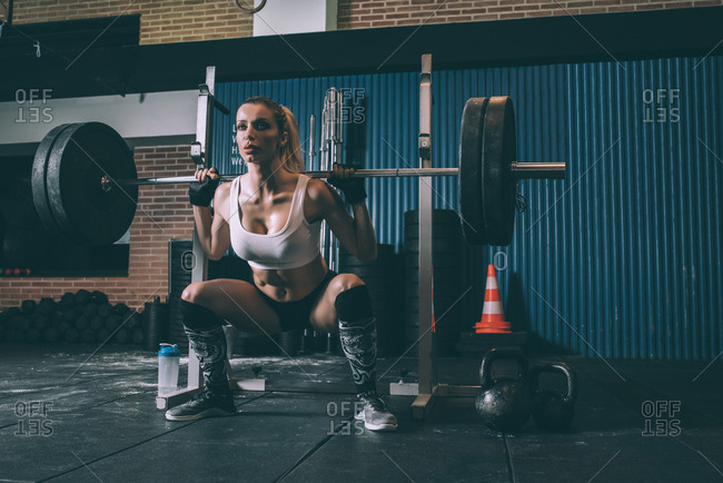 Fit blonde woman training lifting a bar weights in gym