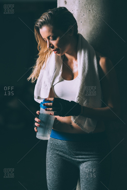 Fit blonde tired woman resting and drinking after training working out in Gym