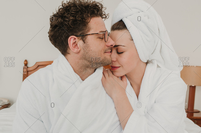 Side view of happy man and woman in bathrobes cuddling on bed.