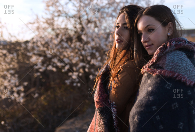 Pretty young women wrapped in plaid standing at blooming tree in nature.
