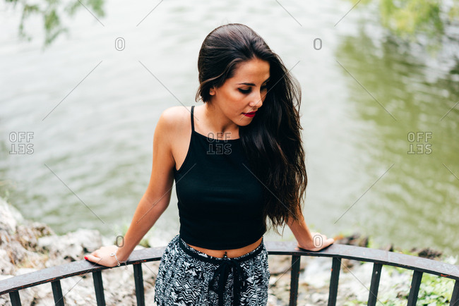Brunette woman leaning on handrail at river
