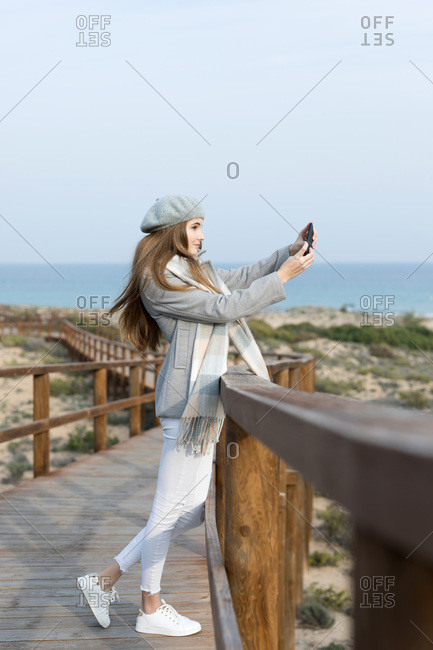 Cheerful woman with smartphone on boardwalk