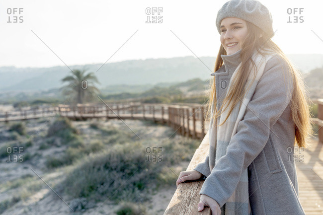 Cheerful woman standing at boardwalk